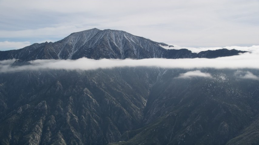 5K stock footage aerial video of tall mountain peak ringed by clouds in the San Jacinto Mountains, California Aerial Stock Footage   AX0010_086