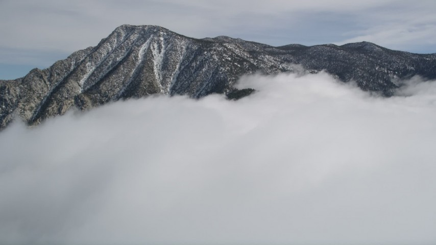 5K stock footage aerial video tilt from snowy mountain to reveal tall peak in the San Jacinto Mountains in winter, California Aerial Stock Footage | AX0010_093
