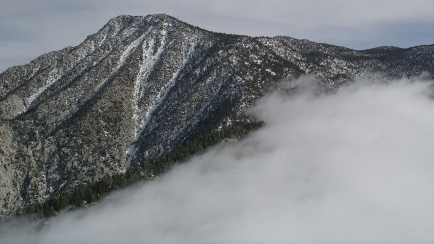 5K stock footage aerial video approach a peak with light snow in the San Jacinto Mountains, California Aerial Stock Footage | AX0010_095