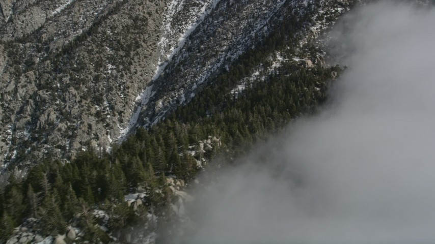 5K aerial video approach a ridge with snow and clouds in the San Jacinto Mountains in wintertime, California Aerial Stock Footage | AX0010_096