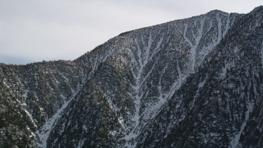 5K aerial video orbit a mountain peak with light winter snow in the San Jacinto Mountains, California Aerial Stock Footage | AX0010_101