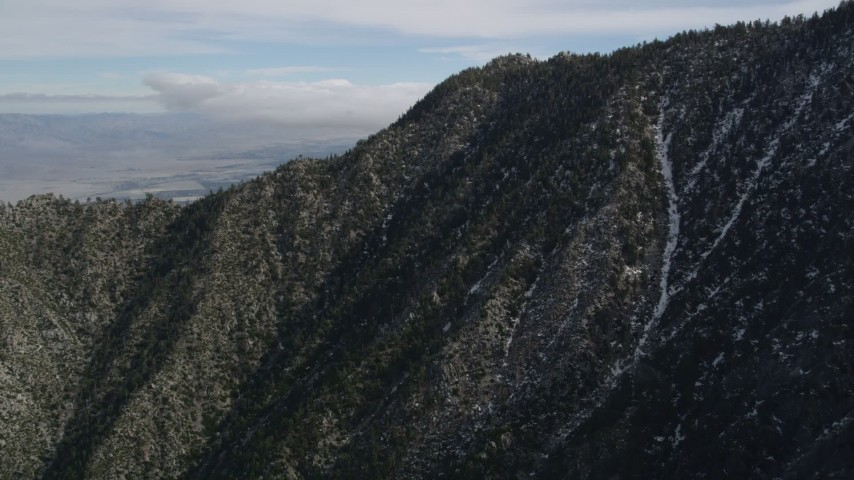 5K stock footage aerial video fly over rugged slopes with patches of snow in the San Jacinto Mountains, California Aerial Stock Footage | AX0010_102