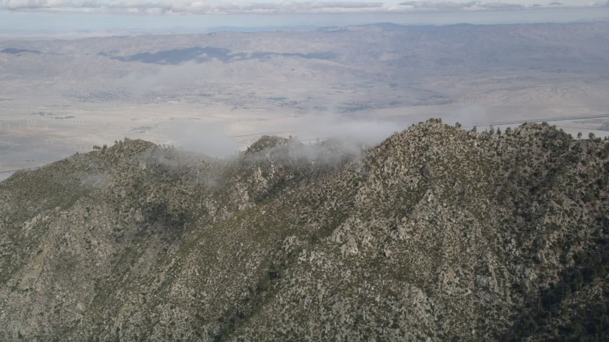 5K stock footage aerial video of rugged mountain ridge in the San Jacinto Mountains with Coachella Valley in the distance, California Aerial Stock Footage | AX0010_103
