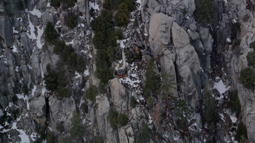 5K aerial video of tracking a gondola heading up a mountain with snow in the San Jacinto Mountains, California Aerial Stock Footage | AX0010_116