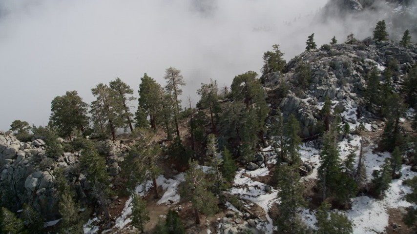 5K stock footage aerial video pan across snow and boulders on a San Jacinto Mountains slope in winter, California Aerial Stock Footage | AX0010_118
