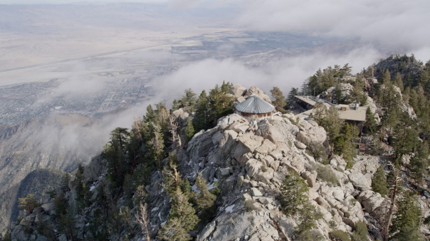 5K stock footage aerial video tilt and fly over rugged mountain slope in the San Jacinto Mountains with light snow, California Aerial Stock Footage | AX0010_121