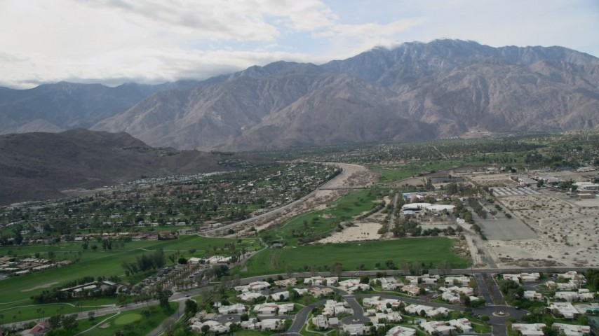 5K stock footage aerial video of suburban neighborhoods in West Palm Springs near tall mountain range, California Aerial Stock Footage | AX0010_142