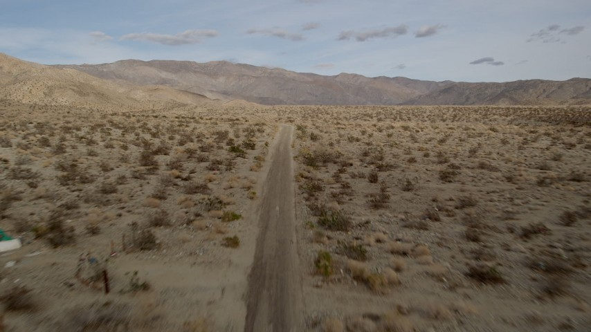 5K stock footage aerial video of following desert road through Joshua Tree National Park, California Aerial Stock Footage | AX0011_008