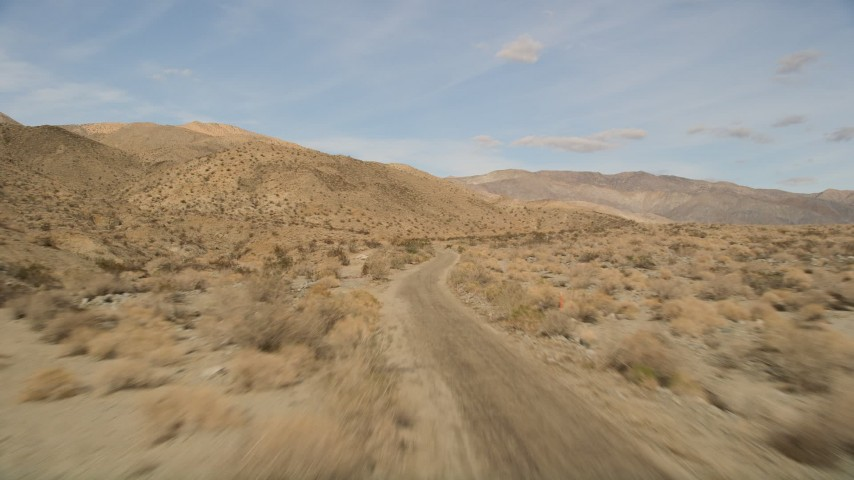 5K stock footage aerial video of following desert road through Joshua Tree National Park, California Aerial Stock Footage   AX0011_008E