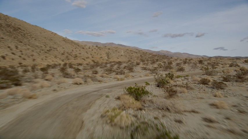 5K stock footage aerial video fly low over a desert road and dry vegetation in Joshua Tree National Park, California Aerial Stock Footage | AX0011_010