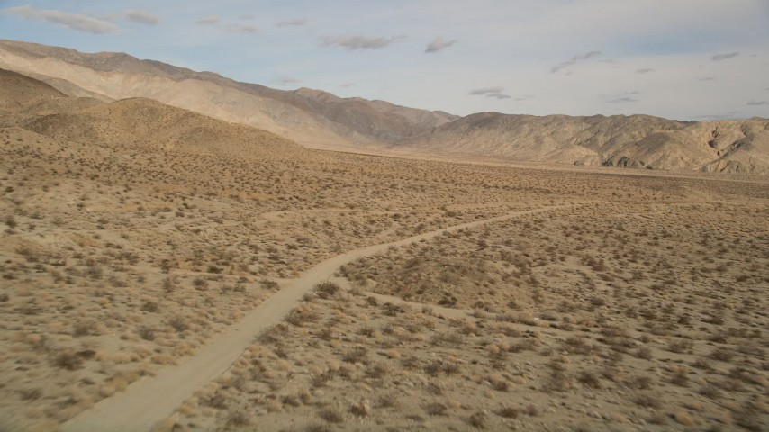 5K aerial video approach and orbit a lonely dirt road in Joshua Tree National Park, California Aerial Stock Footage | AX0011_011