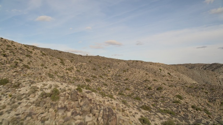 5K stock footage aerial video fly low over desert mountain slope, Joshua Tree National Park, California Aerial Stock Footage | AX0011_023E