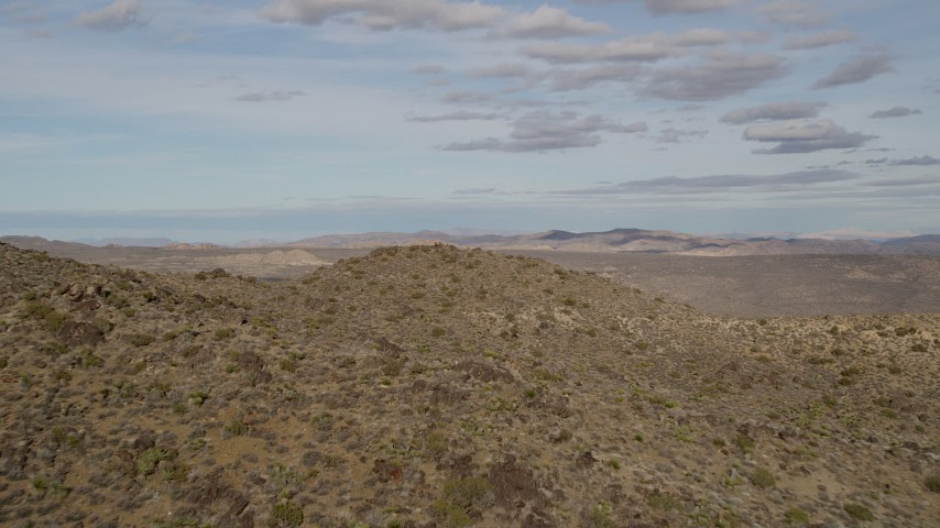 5K stock footage aerial video fly over a hill to reveal desert rock formation, Joshua Tree National Park, California Aerial Stock Footage | AX0011_029