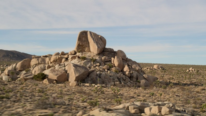 5K stock footage aerial video fly over Joshua Trees and rock formation, Joshua Tree National Park, California Aerial Stock Footage | AX0011_032