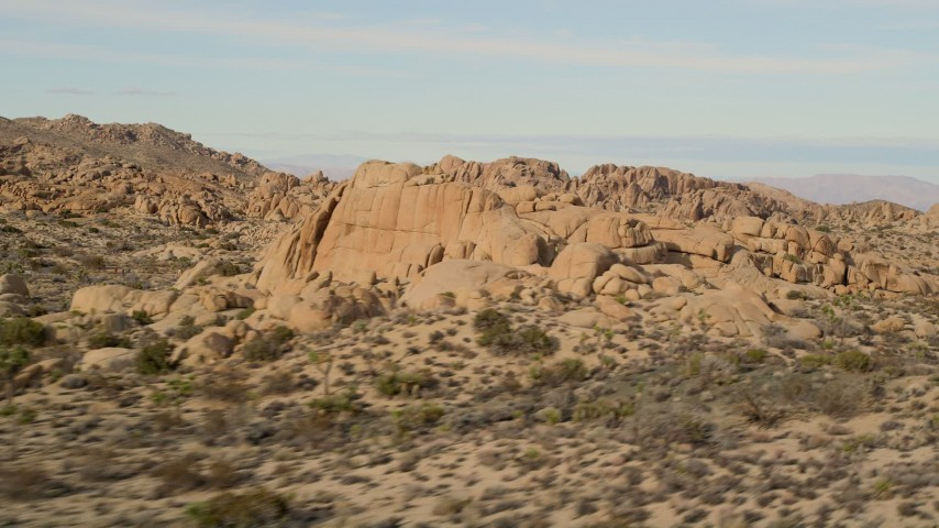 5K stock footage aerial video fly by Joshua Trees and rock formations, Joshua Tree National Park, California Aerial Stock Footage | AX0011_038