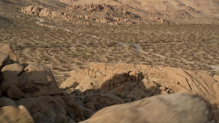 5K stock footage aerial video flyby rock formation revealing desert road, Joshua Tree National Park, California Aerial Stock Footage | AX0011_041