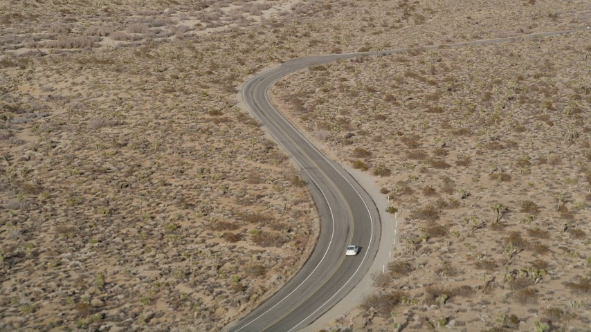 5K stock footage aerial video of tracking a car on a desert road, Joshua Tree National Park, California Aerial Stock Footage | AX0011_043