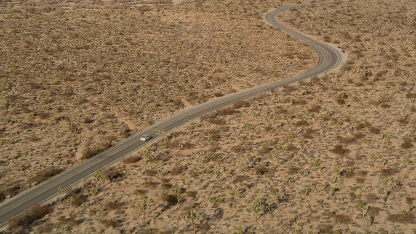 5K stock footage aerial video of tracking a car on a desert road, Joshua Tree National Park, California Aerial Stock Footage   AX0011_043E