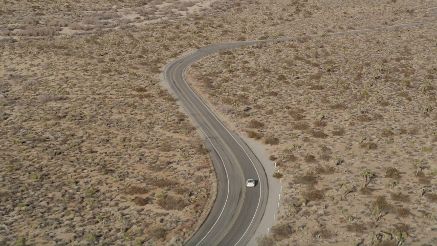 5K stock footage aerial video of tracking a white car traveling on a desert a road, Joshua Tree National Park, California Aerial Stock Footage | AX0011_044