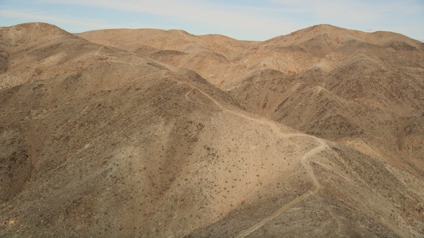 5K stock footage aerial video of following a desert mountain trail, Mojave Desert, California Aerial Stock Footage | AX0011_052