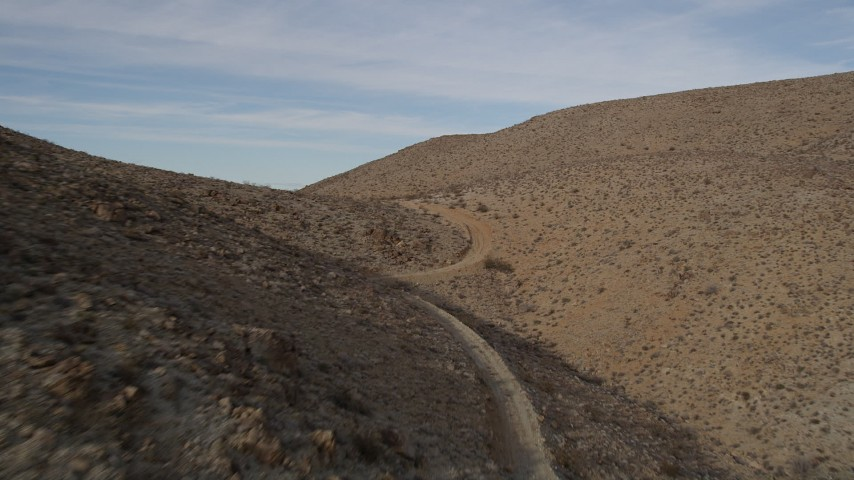 5K stock footage aerial video of following a dirt Road in Mojave Desert, California Aerial Stock Footage | AX0011_054