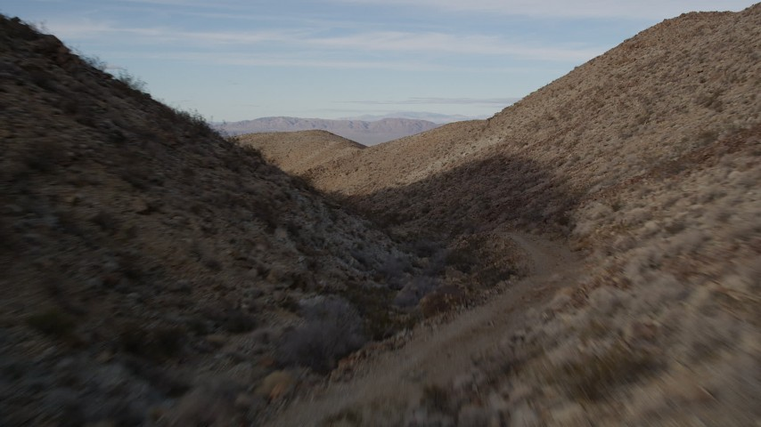 5K stock footage aerial video of flying over a dirt road through a desert canyon, Mojave Desert, California Aerial Stock Footage   AX0011_055