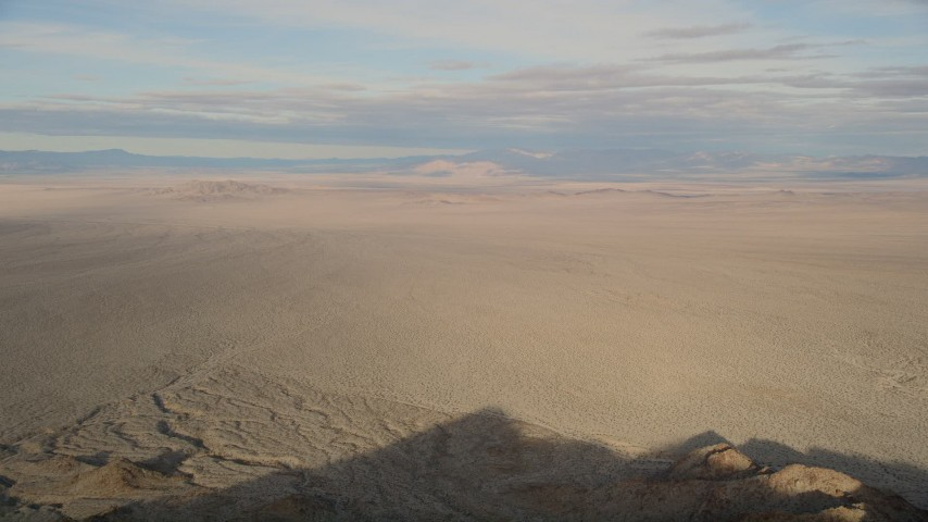 5K stock footage aerial video fly low over a mountain revealing desert plain, Mojave Desert, California Aerial Stock Footage | AX0011_064
