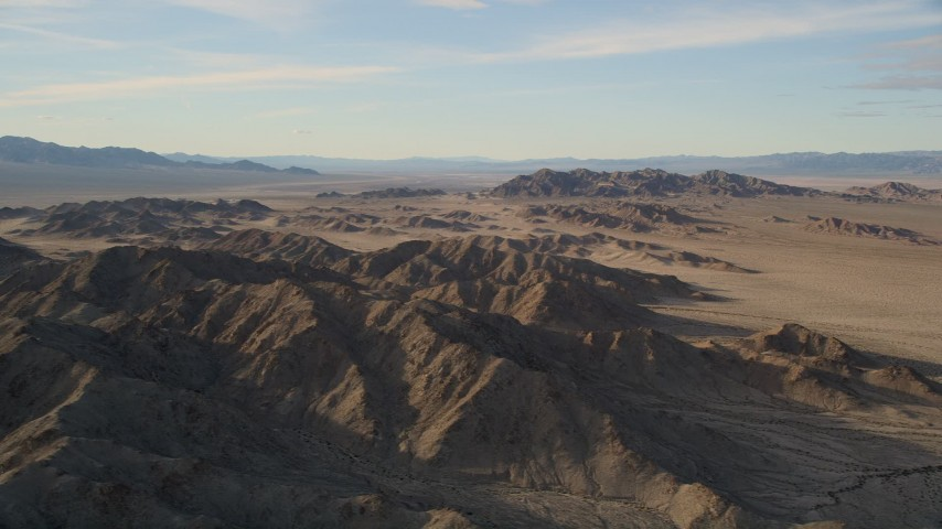 5K stock footage aerial video fly by mountains revealing desert plain, Mojave Desert, California Aerial Stock Footage | AX0011_070