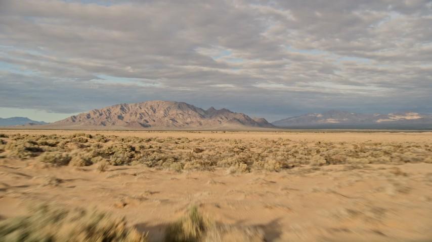 5K stock footage aerial video fly over desert vegetation toward mountains, Mojave Desert, California Aerial Stock Footage | AX0012_004