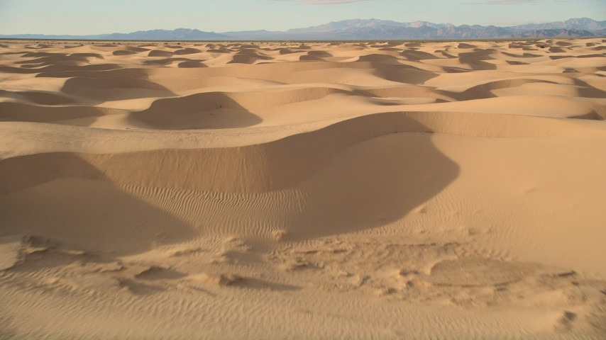 5K aerial video fly low over sand dunes, Kelso Dunes, Mojave Desert, California Aerial Stock Footage AX0012_013