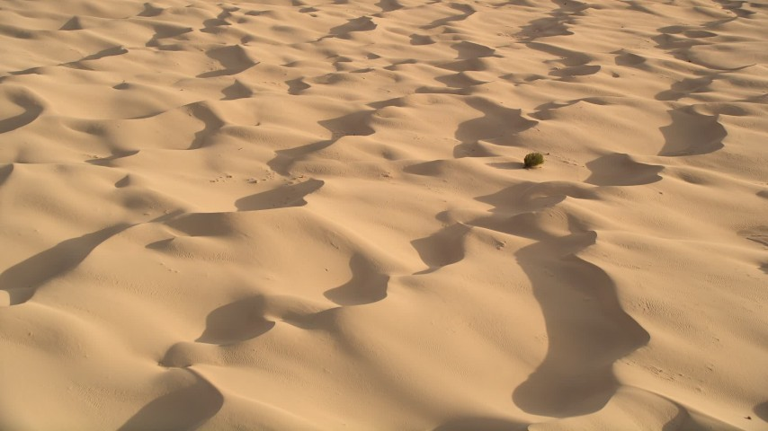 5K stock footage aerial video tilt down to bird's eye of sand dunes, Kelso Dunes, Mojave Desert, California Aerial Stock Footage | AX0012_017E