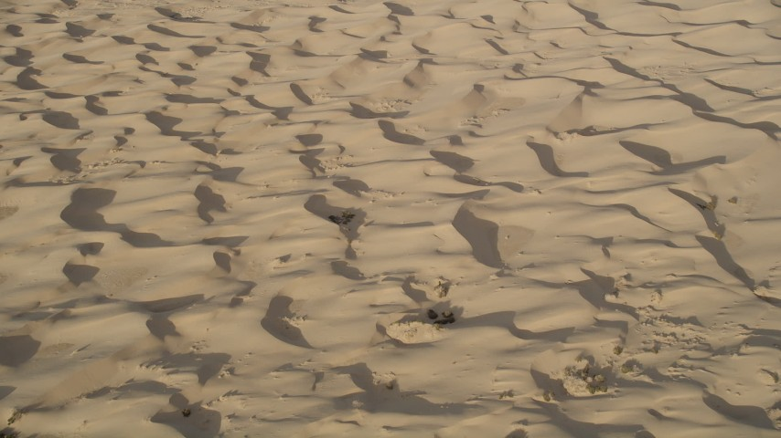 5K stock footage aerial video pan across sand dunes, Kelso Dunes, Mojave Desert, California Aerial Stock Footage | AX0012_021