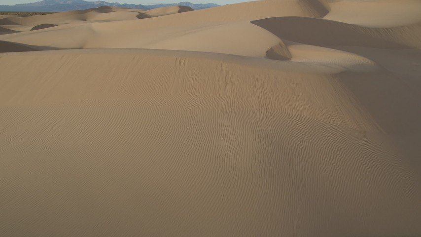 5K aerial video fly low over sand dunes, Kelso Dunes, Mojave Desert, California Aerial Stock Footage | AX0012_034