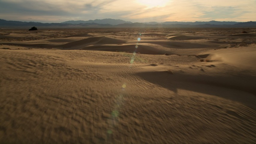 5K stock footage aerial video of flying over sand dunes to open desert, Kelso Dunes, Mojave Desert, California Aerial Stock Footage AX0012_037