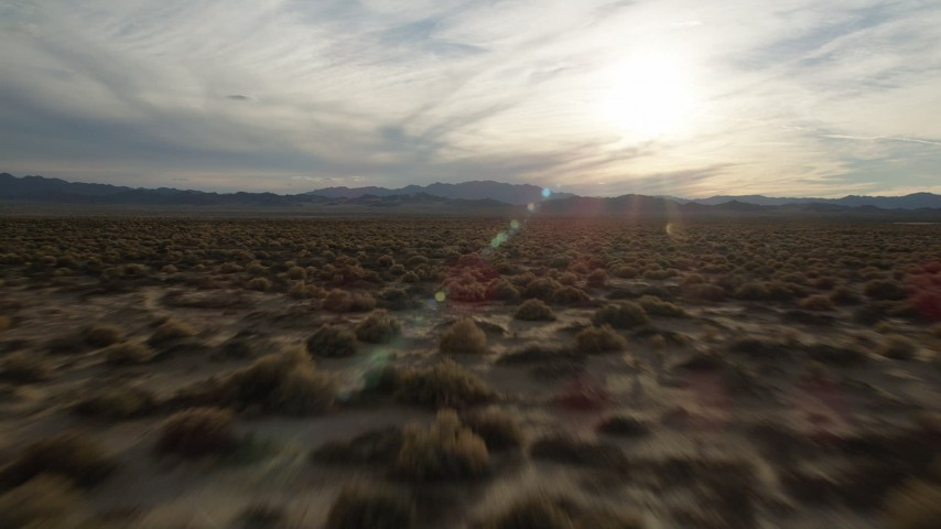 5K stock footage aerial video fly low over desert plain toward the sun, Mojave Desert, California Aerial Stock Footage | AX0012_040