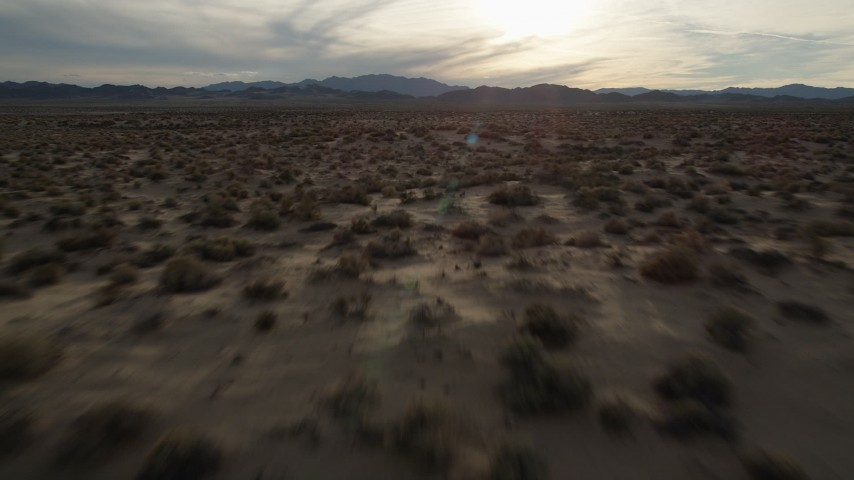 5K stock footage aerial video fly low over desert plain, Mojave Desert, California, sunset Aerial Stock Footage | AX0012_042
