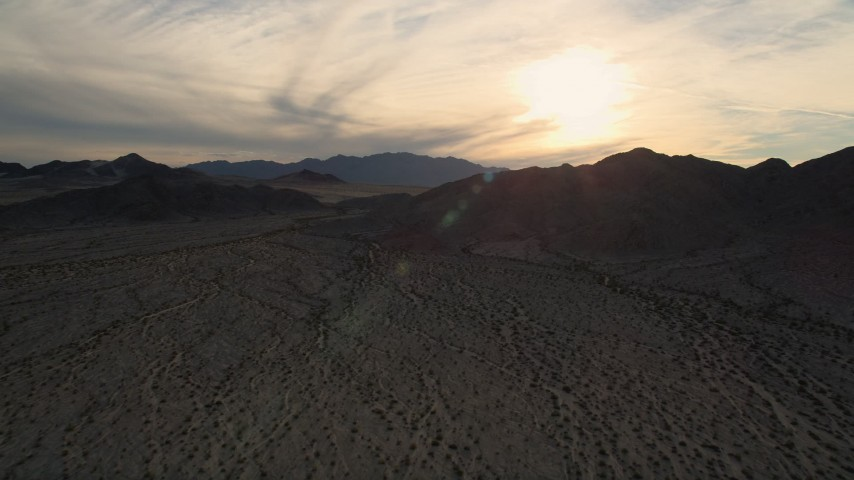 5K aerial video approach desert mountains, Mojave Desert, California, sunset Aerial Stock Footage | AX0012_043