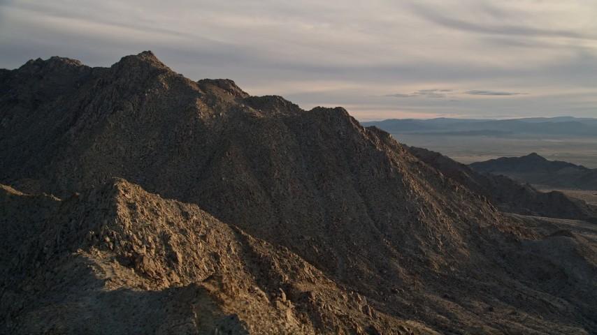 5K stock footage aerial video orbiting a desert mountain peak, Mojave Desert, California, sunset Aerial Stock Footage | AX0012_046