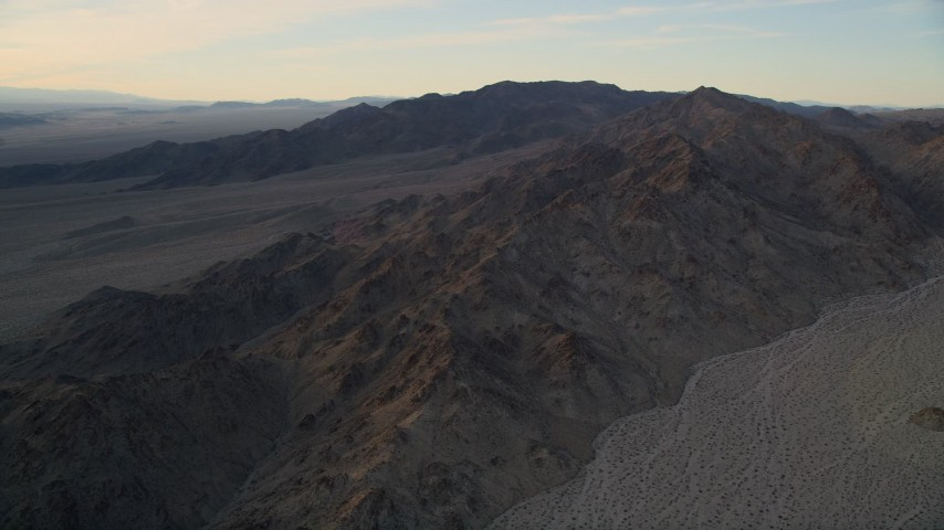 5K stock footage aerial video fly by a desert mountain range, Mojave Desert, California, sunset Aerial Stock Footage | AX0012_050
