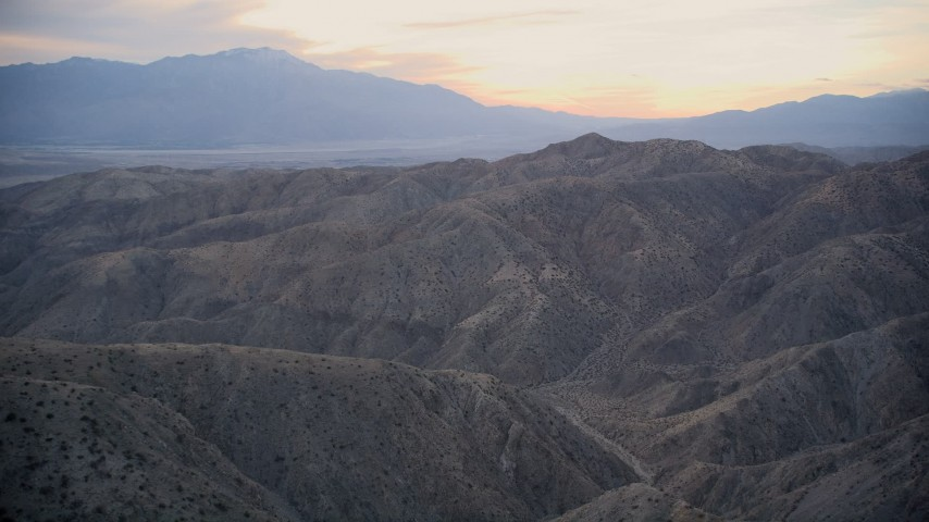 5K stock footage aerial video fly over canyons and desert mountains, Mojave Desert, California, sunset Aerial Stock Footage | AX0012_063