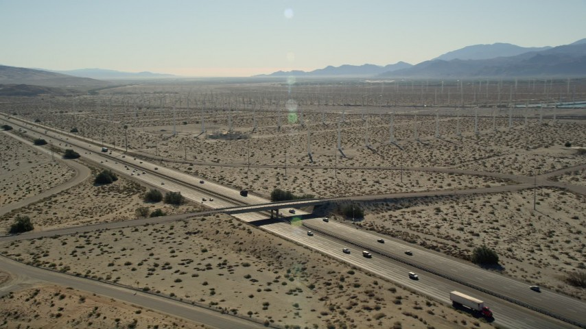 5K stock footage aerial video of interstate cutting through desert wind farm, San Gorgonio Pass Wind Farm, California Aerial Stock Footage | AX0013_019