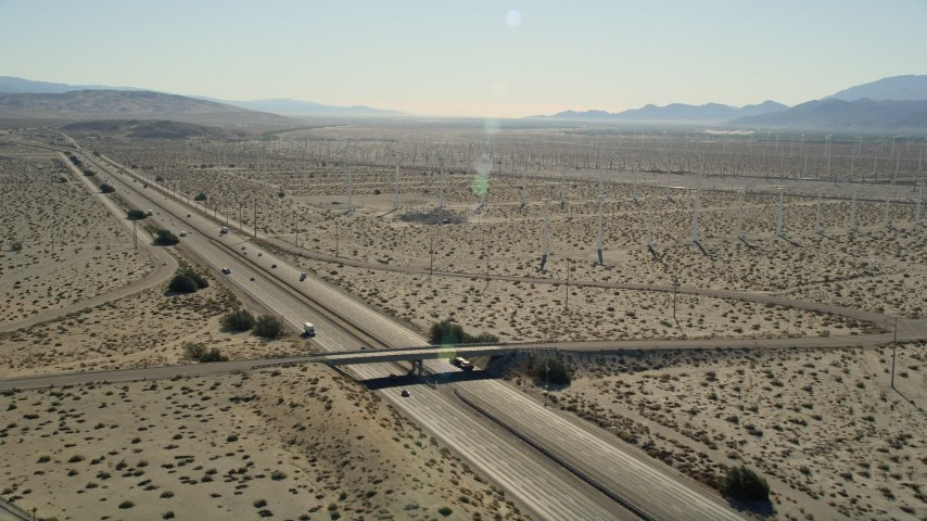5K stock footage aerial video of flying over an interstate passing through desert and a windmill farm, Palm Springs, California Aerial Stock Footage | AX0013_024