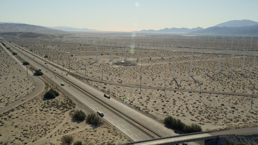 5K stock footage aerial video fly over interstate toward windmills, San Gorgonio Pass Wind Farm, California Aerial Stock Footage | AX0013_025