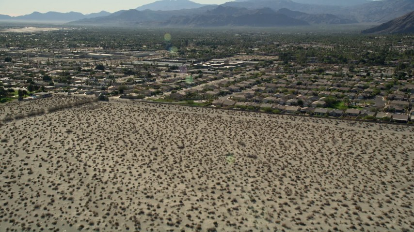 5K aerial video tilt up from desert revealing residential neighborhoods, North Palm Springs, California Aerial Stock Footage | AX0013_032