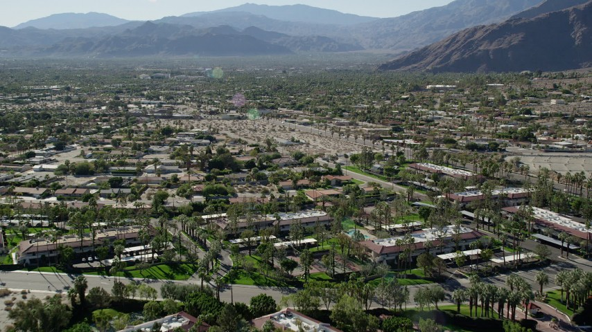 5K aerial video fly over apartment buildings toward residential road, Palm Springs, California Aerial Stock Footage | AX0013_033