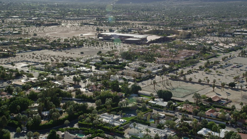 5K stock footage aerial video of fly over residential neighborhoods toward a convention center, West Palm Springs, California Aerial Stock Footage | AX0013_037