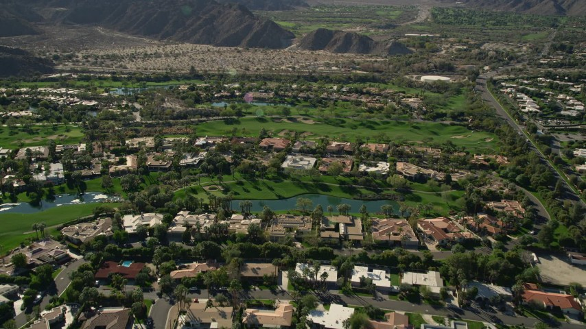 5K stock footage aerial video tilt to upscale homes surrounded by a golf course, Indian Wells, California Aerial Stock Footage | AX0013_075