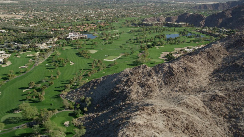 5K stock footage aerial video fly by a golf course at the base of a mountain, Indian Wells, California Aerial Stock Footage | AX0013_078