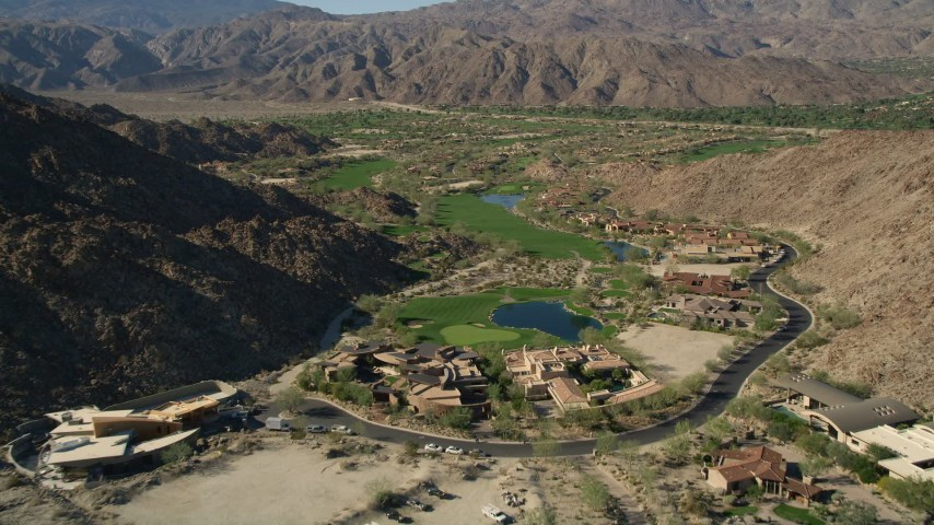 5K stock footage aerial video fly over upscale homes toward golf course among mountains, Indian Wells, California Aerial Stock Footage | AX0013_082