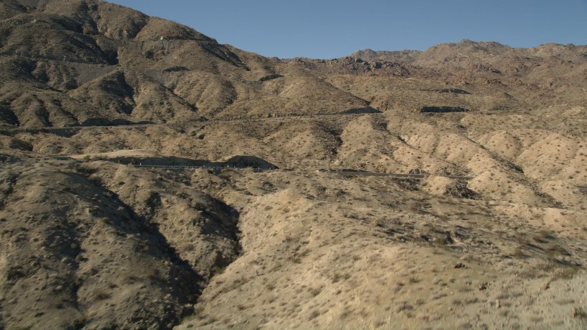 5K stock footage aerial video approach a mountain peak revealing a highway, San Jacinto Mountains, California Aerial Stock Footage | AX0014_002
